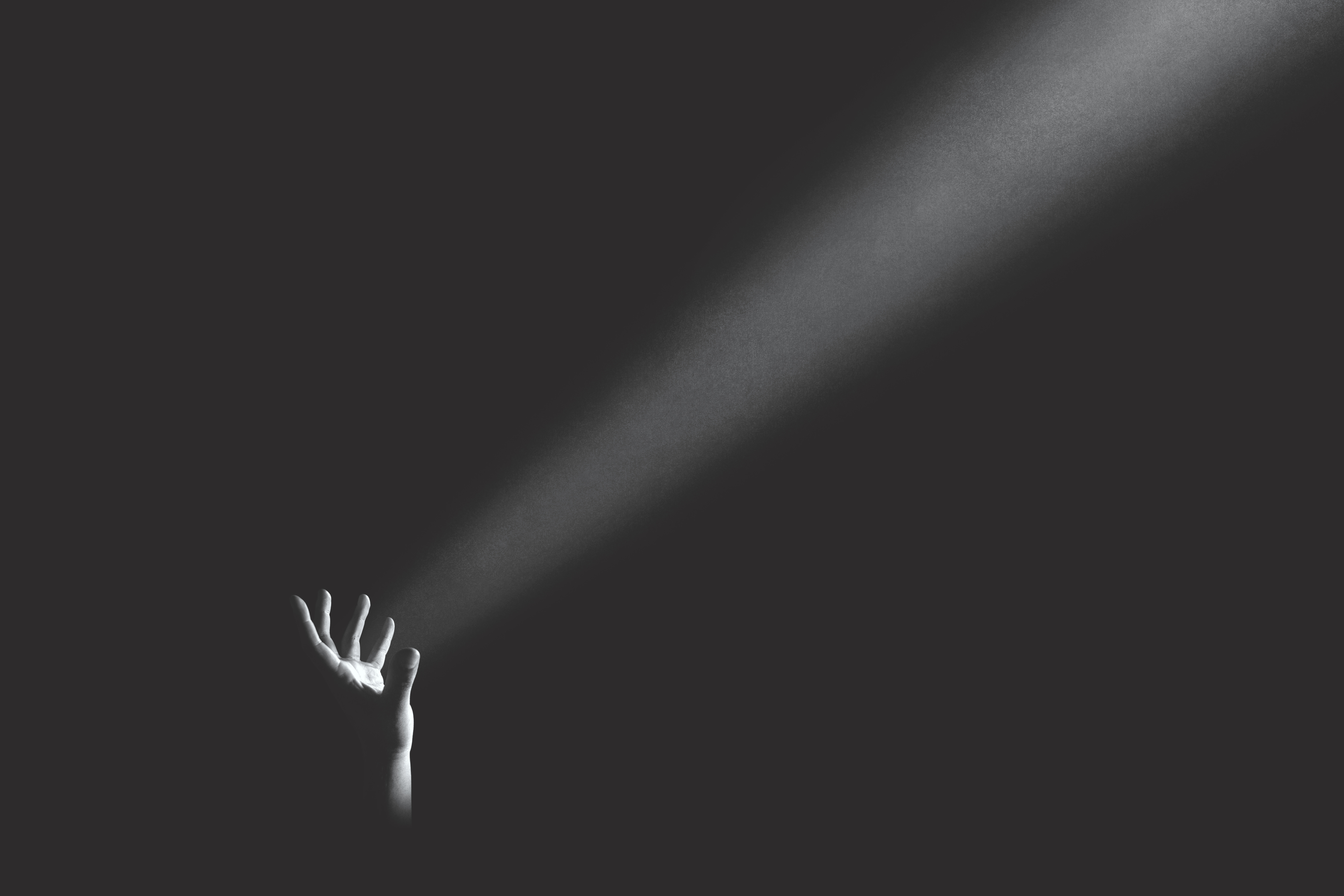A hand projecting light into darkness
